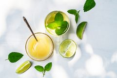 Lime tea with mint in a glass cup and honey on a white background. Top view lime tea with mint in a glass cup and honey on a white background with sunbeams royalty free stock image