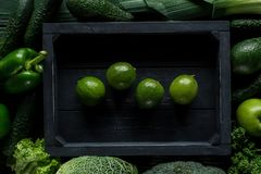 Top view of lime in wooden box between green vegetables, healthy. Eating concept stock images