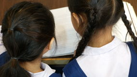 Top view of little Asian students with uniforms reading book in library together stock video
