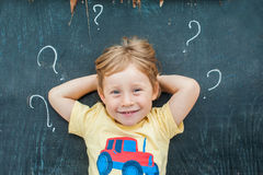 Top view of a little blond kid boy with question mark on blackboard. Concept for confusion, brainstorming and choice.  Royalty Free Stock Images