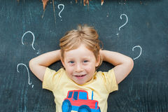 Top view of a little blond kid boy with question mark on blackboard. Concept for confusion, brainstorming and choice.  Stock Images
