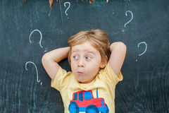 Top view of a little blond kid boy with question mark on blackboard. Concept for confusion, brainstorming and choice Royalty Free Stock Images