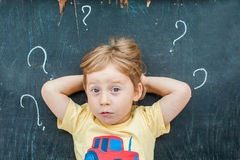 Top view of a little blond kid boy with question mark on blackboard. Concept for confusion, brainstorming and choice Stock Photography