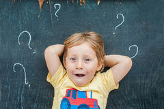Top view of a little blond kid boy with question mark on blackboard. Concept for confusion, brainstorming and choice.  Stock Photography