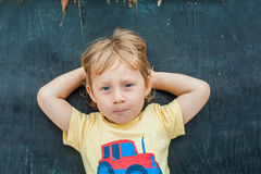 Top view of a little blond kid boy with space for text and symbols on the old wooden background. Concept for confusion, brainstorm Royalty Free Stock Photography