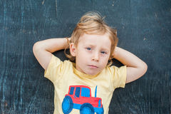 Top view of a little blond kid boy with space for text and symbols on the old wooden background. Concept for confusion, brainstorm Stock Images