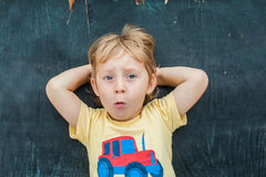 Top view of a little blond kid boy with space for text and symbols on the old wooden background. Concept for confusion, brainstorm Stock Photography