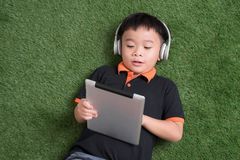 Top view of little boy in headphones using a digital tablet and smiling while lying on green grass stock photography