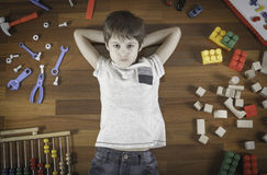 Top view of little boy lying with hands behind his head on the wooden floor and many colorful toys around him. Royalty Free Stock Images