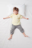 Top view of little boy sleeping in Star pose Royalty Free Stock Images
