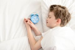 Top view of little boy sleeping in white bed with alarm clock near his head. Stock Photos