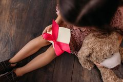 top view of little child holding giftbox in shape of heart while sitting royalty free stock photos