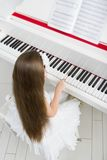Top view of little child in white dress playing piano Stock Image