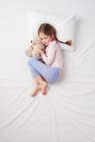 Top view of little cute girl sleeping with teddy royalty free stock photography