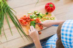 TOP VIEW: Little girl in cook clothes cuts a cucumber on a board on a kitchen Royalty Free Stock Photos