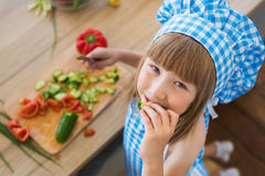 TOP VIEW: Little girl in cook clothes eats a cucumber, smiles and looks to the camera Stock Photography