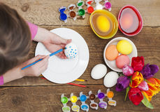 Top view of little girl decorating Easter eggs. Top view of little girl holding paintbrush and decorating Easter eggs with watercolors over plate, bunch of Stock Images
