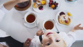 Top view of little girl drinks tea and looking up during breakfast stock photography