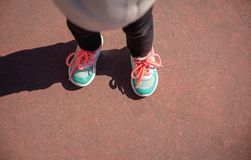 Little girl with sneakers and leggins training outdoors. Top view of little girl legs with sneakers and black leggins training outdoors Royalty Free Stock Images
