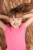 Top view of a little girl lying on back. Top view of a funny little girl lying on her back on wooden floor with moustache made of parsley leaves Stock Image