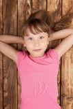 Top view of a little girl lying on back. Top view of a little girl lying on her back on wooden floor with hands over head Royalty Free Stock Photography