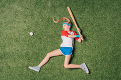 Top view of little girl pretending playing baseball on grass Stock Image