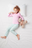 Top view of little girl sleeping with teddy bear Stock Images