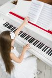 Top view of little girl in white dress playing piano Royalty Free Stock Photography