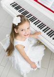 Top view of little musician in white dress playing piano. Top view of little girl in white dress playing piano. Concept of music study and creative hobby royalty free stock photo