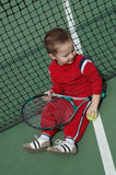Top view of a little player. Adorable little boy sitting next to the tennis net with a tennis racket and tennis ball in his hands Royalty Free Stock Photo