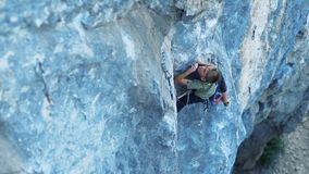 Top view of little scared and tensed boy rock climber, climbing on a cliff, searching, reaching and gripping holds.