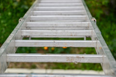Top view of a long silver aluminum ladder leaning against the wall of the house. Close up view from top of tall step ladder Royalty Free Stock Images