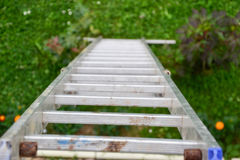 Top view of a long silver aluminum ladder leaning against the wall of the house. Close up view from top of tall step ladder Royalty Free Stock Photo