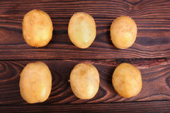Top view of a lot of fresh and organic potatoes on a dark brown wooden background. New potatoes, close-up. Summer harvest. Stock Images