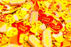 Top view of lots of colourful foam stickers depicting hearts, butterflies and cupcakes. Focus on two hearts. Summer or joy concept royalty free stock photos