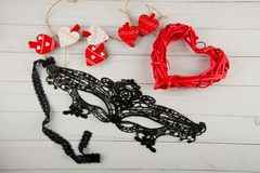 Top view on love decorations. Small wooden hearts, big red rattan heart and balck lace mask stock photo