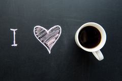 Top view of love heart doodle drawing on chalkboard. With cup of coffee stock images