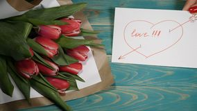 Top view of a love message note and tulips flowers bouquet on a wooden table. Love relationship concept. St Valentine s. Day. 4 k stock video