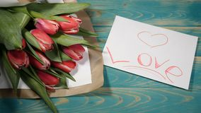 Top view of a Love message note and tulips flowers bouquet on a wooden table. Love relationship concept. Saint. Valentines Day. 4 k stock footage