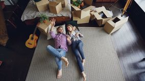 Top view of loving couple lying on bedroom floor in new apartment and talking. Guitar, packed things in carton boxes