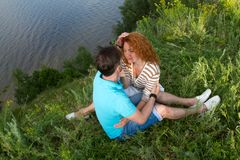 Top view of loving couple relaxing on grass and hugging. relationships and feelings concept. Couple on picnic hugging on grass stock photography