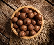 Macadamia nuts on wooden table. Royalty Free Stock Image