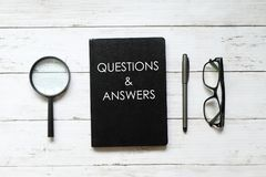 Top view of magnifying glass,pen,eyeglasses and notebook written with QUESTIONS & ANSWERS on white wooden background stock images