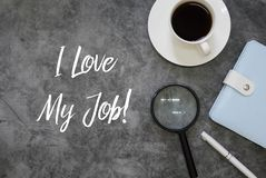 Top view of magnifying glasses,pen,notebook and coffee on grey grunge floor written with I Love My Job royalty free stock photos