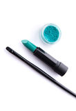 Top view of makeup brush, lipstick and eye shadow in bold teal g Royalty Free Stock Photography