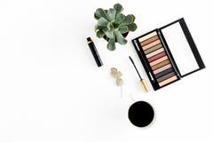 Top view makeup table. Eyeshadow, mascara, succulents cup of coffee. Top view makeup table. Eyeshadow, mascara, succulents, eucalyptus and cup of coffee on white stock image