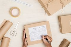 Top view of making notes in delivery receipt among parcels at table royalty free stock photos