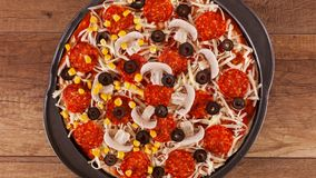Top view of making a pizza with ingredients appearing on the baking plate stock footage