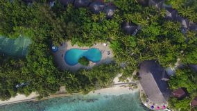 Top view of Maldives island, camera is descending to the swimming pool on luxury hotel. Aerial video of resort with lots stock video