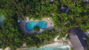 Top view of Maldives island, camera is rising over the swimming pool on luxury hotel. Aerial video of resort with lots stock video footage